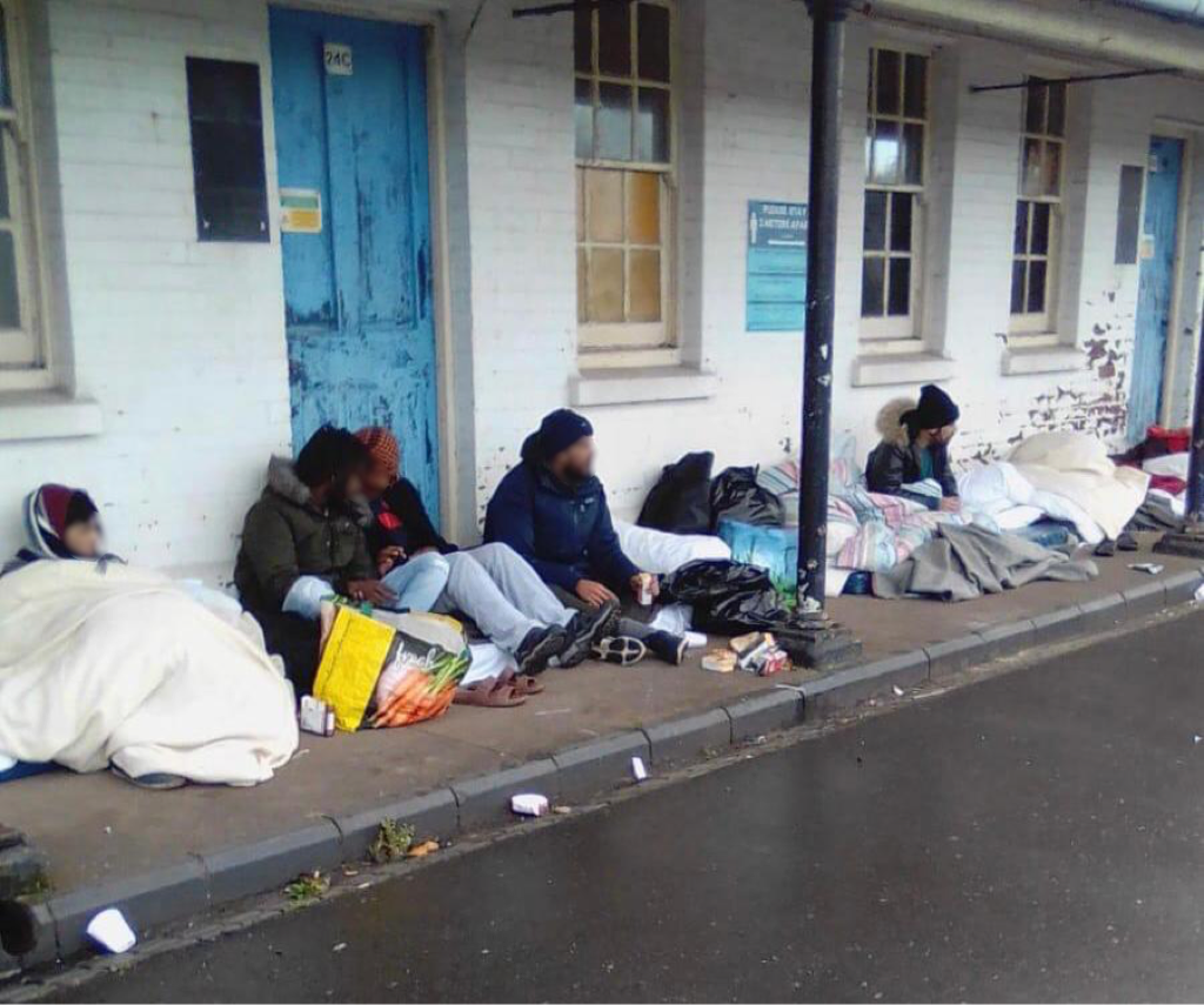 Refugees sit outside a barracks building with makeshift bedding