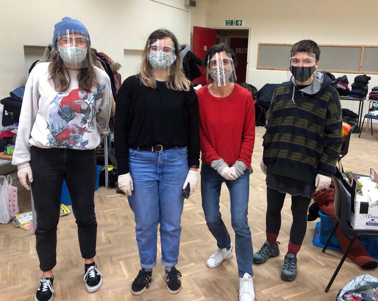 Four volunteers stand together, wearing masks