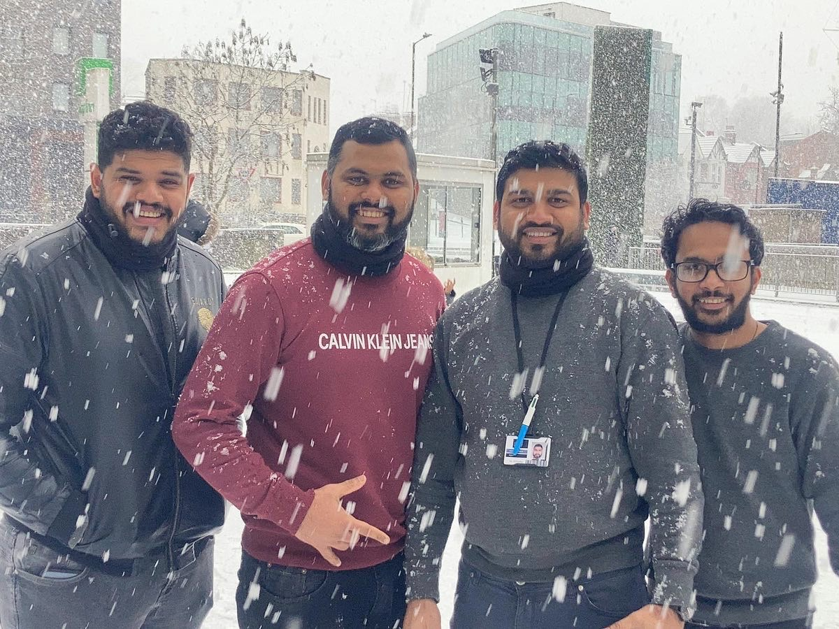 An image of four men smiling in the snow