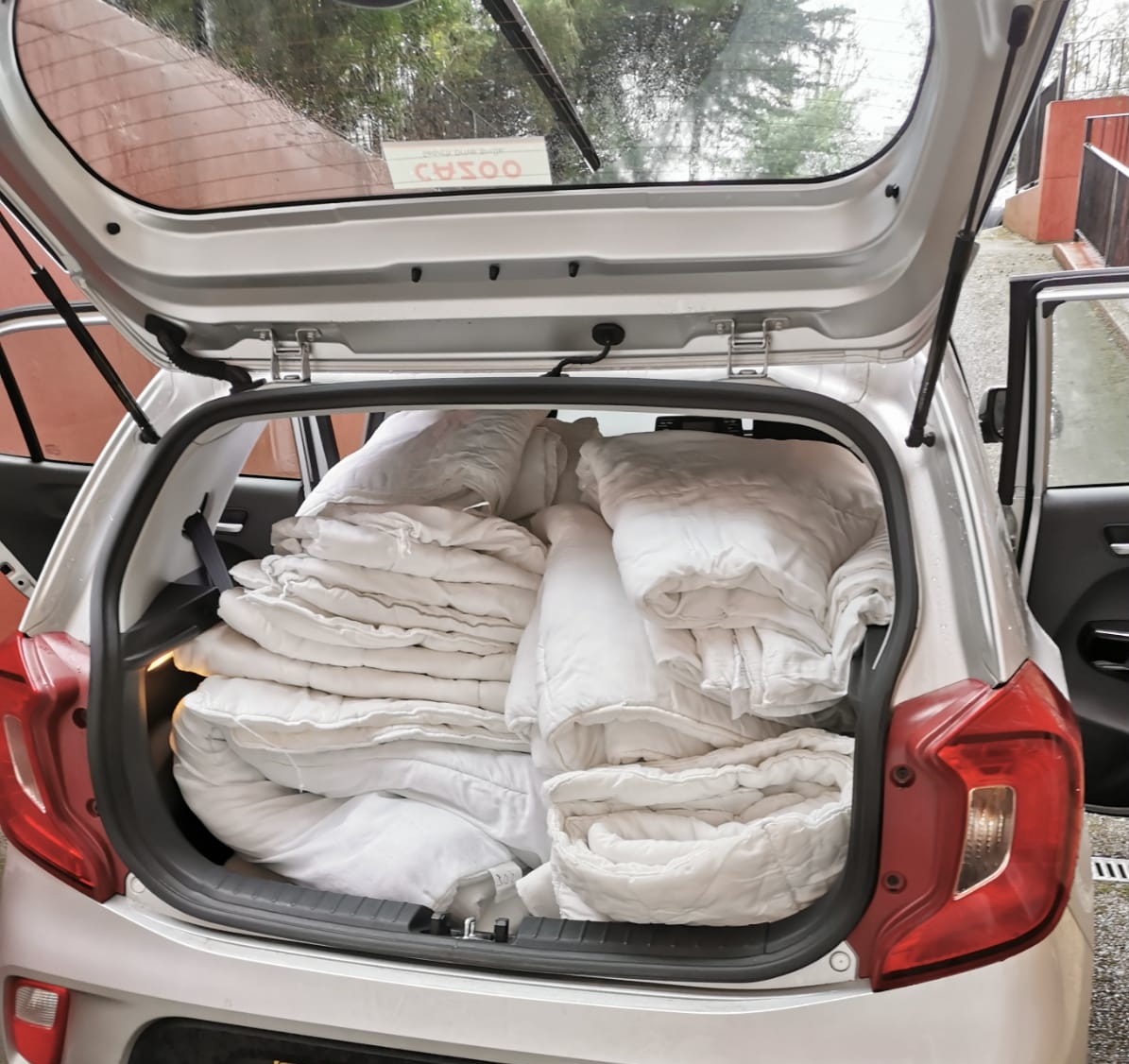 car boot filled with blankets and duvets