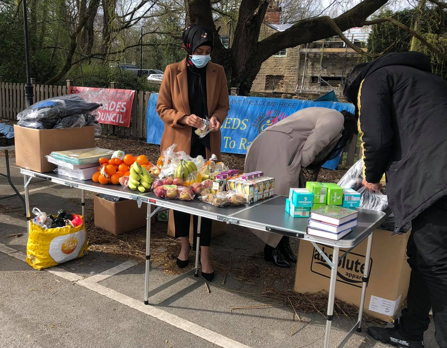 Volunteers wearing medical grade masks stand behind a table of food and items for distribution
