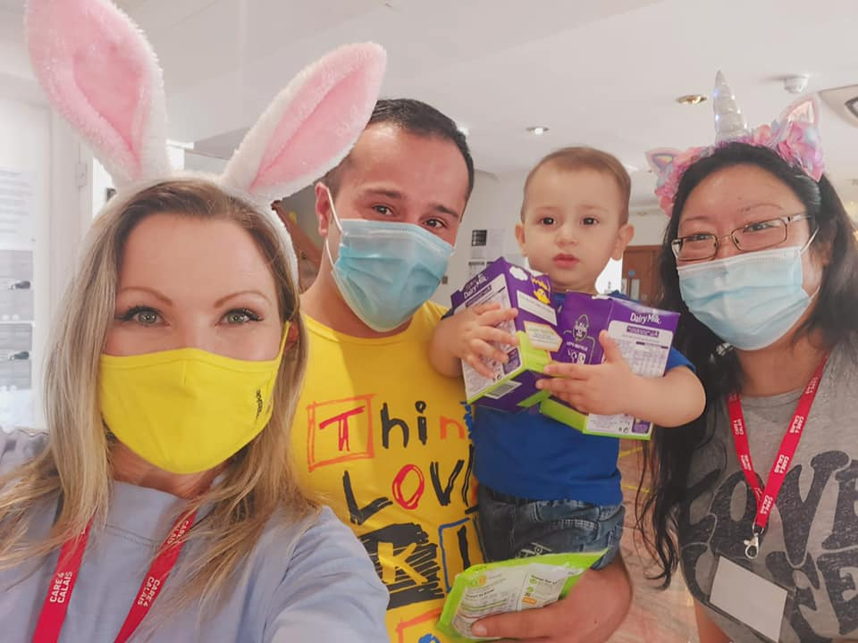 Two women, a man and a baby holding easter eggs and smiling at the camera. The adults are wearing masks and the women are wearing rabbit ears.