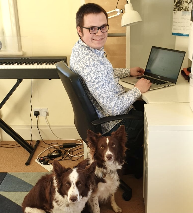 A man wearing a light blue shirt and glasses sits at a desk working at a laptop. Two dogs sit behind him.